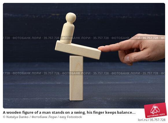 A wooden figure of a man stands on a swing, his finger keeps balance... Стоковое фото, фотограф Natalya Danko / easy Fotostock / Фотобанк Лори