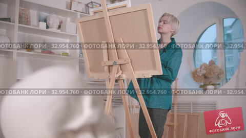 A young blonde woman artist drawing a skull and other figures from the table. Стоковое видео, видеограф Константин Шишкин / Фотобанк Лори