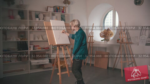 A young blonde woman artist drawing sketch on the canvas and listen music in the headphones. Стоковое видео, видеограф Константин Шишкин / Фотобанк Лори