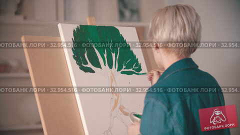 A young blonde woman draws a painting with a green color on the canvas. Стоковое видео, видеограф Константин Шишкин / Фотобанк Лори