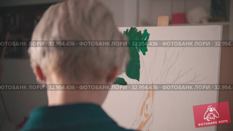 A young blonde woman painting with a green color on the canvas. Стоковое видео, видеограф Константин Шишкин / Фотобанк Лори