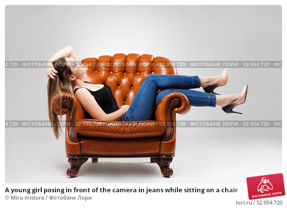 A young girl posing in front of the camera in jeans while sitting on a chair. Стоковое фото, фотограф Miru misiura / Фотобанк Лори