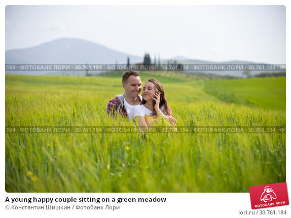 Купить «A young happy couple sitting on a green meadow», фото № 30761184, снято 24 апреля 2019 г. (c) Константин Шишкин / Фотобанк Лори