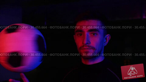 A young man on the underground parking spinning the ball on his finger in neon lighting. Looking in the camera. Стоковое видео, видеограф Константин Шишкин / Фотобанк Лори