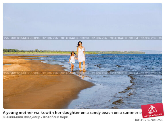 A young mother walks with her daughter on a sandy beach on a summer sunny day at sunset. Стоковое фото, фотограф Акиньшин Владимир / Фотобанк Лори