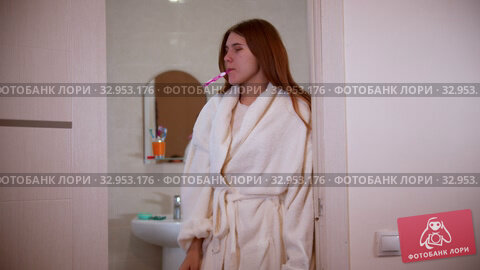 A young woman brushing her teeth at the morning wearing a bathrobe standing in the doorway. Стоковое видео, видеограф Константин Шишкин / Фотобанк Лори