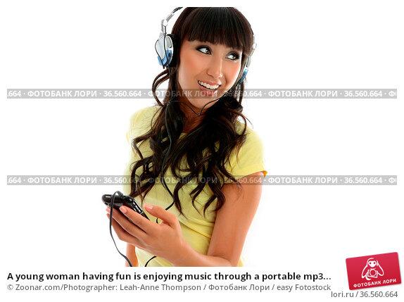 A young woman having fun is enjoying music through a portable mp3... Стоковое фото, фотограф Zoonar.com/Photographer: Leah-Anne Thompson / easy Fotostock / Фотобанк Лори