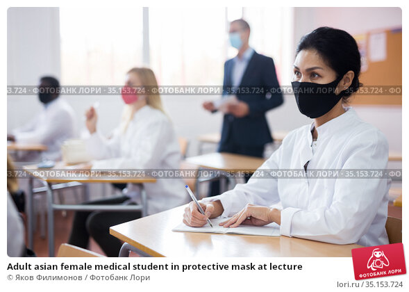 Adult asian female medical student in protective mask at lecture. Стоковое фото, фотограф Яков Филимонов / Фотобанк Лори