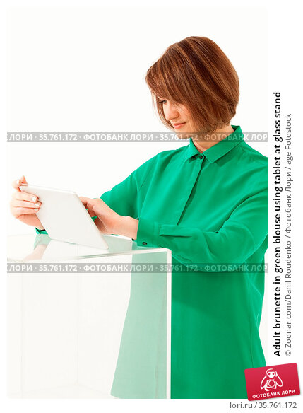 Adult brunette in green blouse using tablet at glass stand. Стоковое фото, фотограф Zoonar.com/Danil Roudenko / age Fotostock / Фотобанк Лори