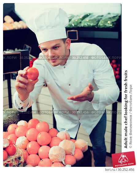 Купить «Adult male chef looking for fresh fruits», фото № 30252456, снято 23 ноября 2016 г. (c) Яков Филимонов / Фотобанк Лори