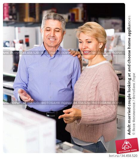 Adult married couple looking at and choose home appliances. Стоковое фото, фотограф Яков Филимонов / Фотобанк Лори