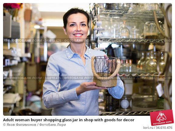 Adult woman buyer shopping glass jar in shop with goods for decor. Стоковое фото, фотограф Яков Филимонов / Фотобанк Лори