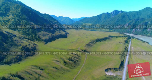Купить «Aerial rural mountain road and meadow at sunny summer morning. Asphalt highway and river.», видеоролик № 30949372, снято 24 ноября 2017 г. (c) Александр Маркин / Фотобанк Лори