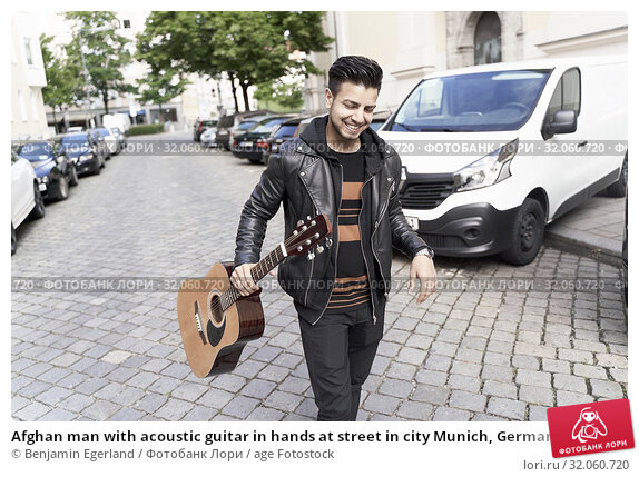 Afghan man with acoustic guitar in hands at street in city Munich, Germany. Стоковое фото, фотограф Benjamin Egerland / age Fotostock / Фотобанк Лори