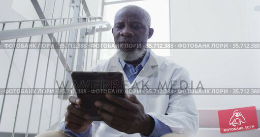 African american male doctor sitting on stairs in hospital using tablet. Стоковое видео, агентство Wavebreak Media / Фотобанк Лори