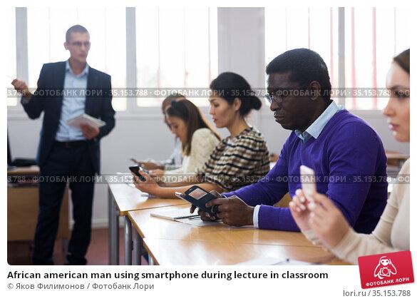 African american man using smartphone during lecture in classroom. Стоковое фото, фотограф Яков Филимонов / Фотобанк Лори