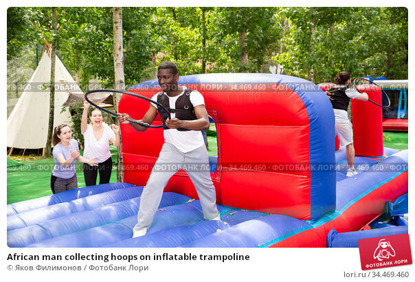African man collecting hoops on inflatable trampoline. Стоковое фото, фотограф Яков Филимонов / Фотобанк Лори