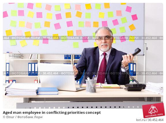 Aged man employee in conflicting priorities concept. Стоковое фото, фотограф Elnur / Фотобанк Лори