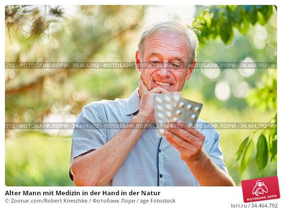 Alter Mann mit Medizin in der Hand in der Natur. Стоковое фото, фотограф Zoonar.com/Robert Kneschke / age Fotostock / Фотобанк Лори