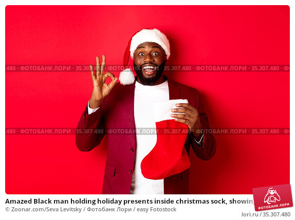 Amazed Black man holding holiday presents inside christmas sock, showing... Стоковое фото, фотограф Zoonar.com/Seva Levitsky / easy Fotostock / Фотобанк Лори
