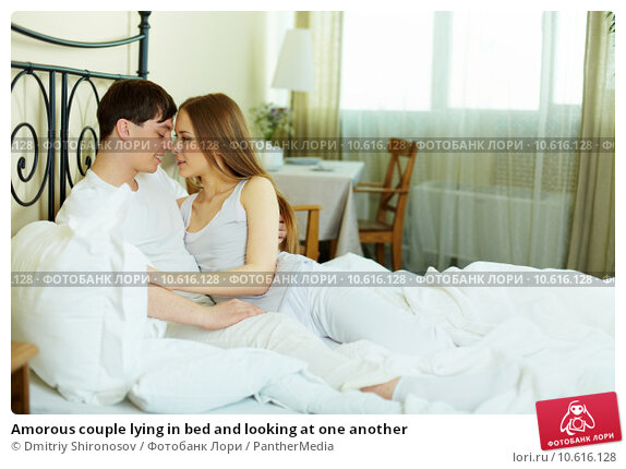 Amorous couple lying in bed and looking at one another. Стоковое фото, фотограф Dmitriy Shironosov / PantherMedia / Фотобанк Лори