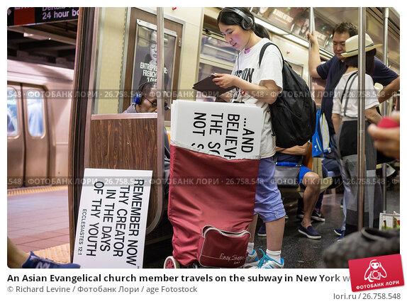 Купить «An Asian Evangelical church member travels on the subway in New York with her signs», фото № 26758548, снято 18 июня 2017 г. (c) age Fotostock / Фотобанк Лори