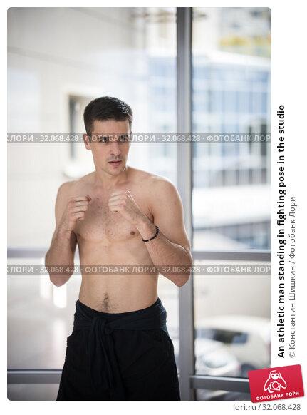 An athletic man standing in fighting pose in the studio. Стоковое фото, фотограф Константин Шишкин / Фотобанк Лори