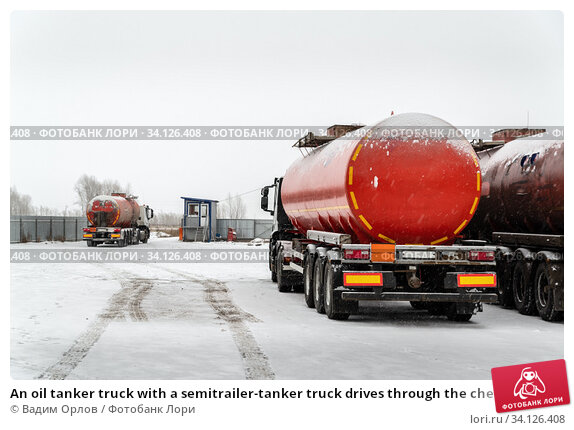 Купить «An oil tanker truck with a semitrailer-tanker truck drives through the checkpoint from the territory of the motor transport base. The picture was taken in Russia in winter», фото № 34126408, снято 16 декабря 2019 г. (c) Вадим Орлов / Фотобанк Лори