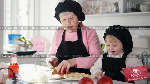 An old woman with a little girl making desserts in the kitchen. An old woman cutting an apple. Стоковое видео, видеограф Константин Шишкин / Фотобанк Лори
