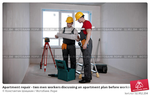 Apartment repair - two men workers discussing an apartment plan before working on it. Стоковое фото, фотограф Константин Шишкин / Фотобанк Лори