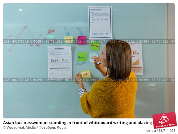 Asian businesswoman standing in front of whiteboard writing and placing memo notes. Стоковое фото, агентство Wavebreak Media / Фотобанк Лори