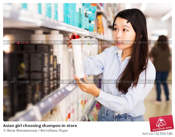 Asian girl choosing shampoo in store. Стоковое фото, фотограф Яков Филимонов / Фотобанк Лори