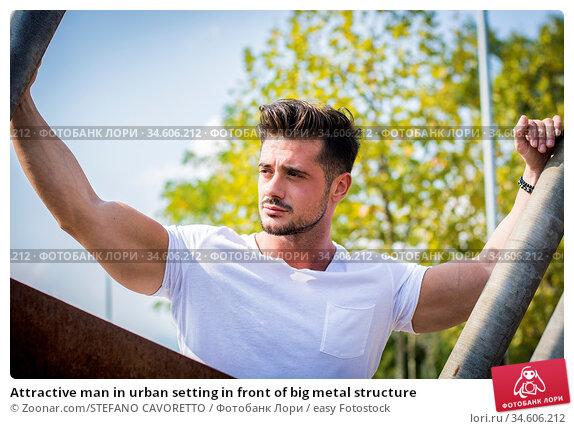 Attractive man in urban setting in front of big metal structure. Стоковое фото, фотограф Zoonar.com/STEFANO CAVORETTO / easy Fotostock / Фотобанк Лори