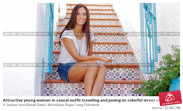 Купить «Attractive young woman in casual outfit traveling and posing on colorful street stairs sitting with smarpthone and looking happily at camera.», фото № 32562748, снято 5 июля 2020 г. (c) easy Fotostock / Фотобанк Лори