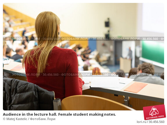 Audience in the lecture hall. Female student making notes. Стоковое фото, фотограф Matej Kastelic / Фотобанк Лори