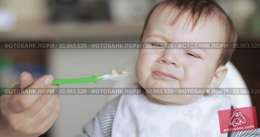 Baby boy fed oatmeal. Стоковое видео, видеограф Потийко Сергей / Фотобанк Лори