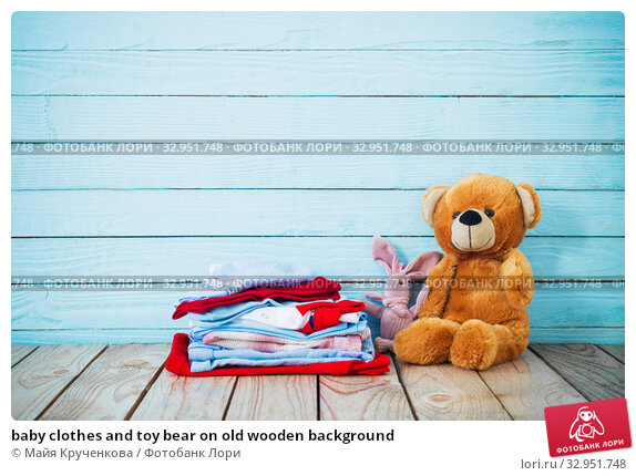 baby clothes and toy bear on old wooden background. Стоковое фото, фотограф Майя Крученкова / Фотобанк Лори