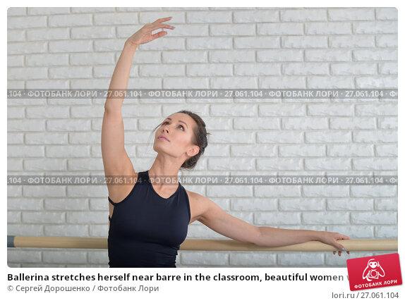Купить «Ballerina stretches herself near barre in the classroom, beautiful women weared in black bodysuit practicing ballet», фото № 27061104, снято 26 апреля 2018 г. (c) Сергей Дорошенко / Фотобанк Лори