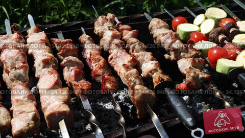 Barbecue meat on skewers, beautifully browned meat on the grill. A pork meat on the grill in the spring garden. Cooking shashlik on the mangal in nature. Shashlik cooking on the coals. Стоковое видео, видеограф Алексей Кузнецов / Фотобанк Лори