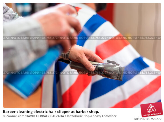 Barber cleaning electric hair clipper at barber shop. Стоковое фото, фотограф Zoonar.com/DAVID HERRAEZ CALZADA / easy Fotostock / Фотобанк Лори