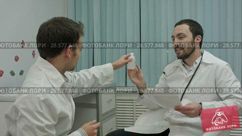 Купить «Bearded doctor shows new drugs to intern», видеоролик № 28577848, снято 24 ноября 2015 г. (c) Vasily Alexandrovich Gronskiy / Фотобанк Лори