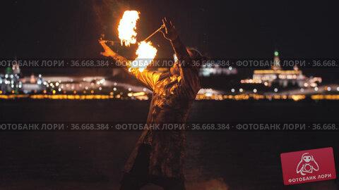 Bearded man performing on fire show - leads burning torches around his head. Стоковое видео, видеограф Константин Шишкин / Фотобанк Лори