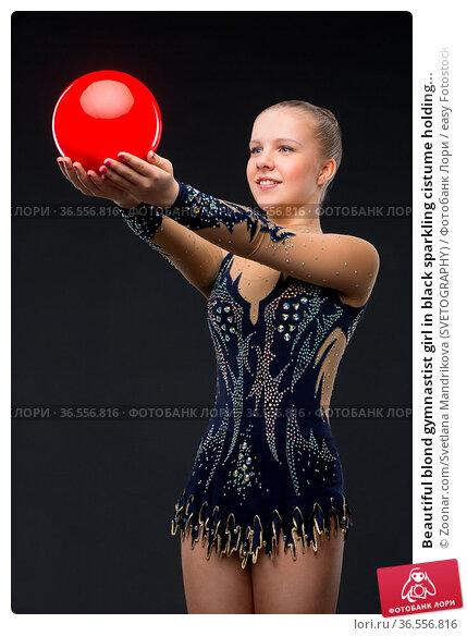 Beautiful blond gymnastist girl in black sparkling cistume holding... Стоковое фото, фотограф Zoonar.com/Svetlana Mandrikova (SVETOGRAPHY) / easy Fotostock / Фотобанк Лори