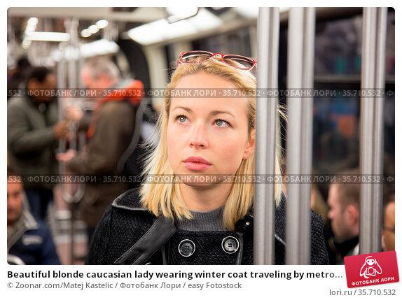 Beautiful blonde caucasian lady wearing winter coat traveling by metro... Стоковое фото, фотограф Zoonar.com/Matej Kastelic / easy Fotostock / Фотобанк Лори