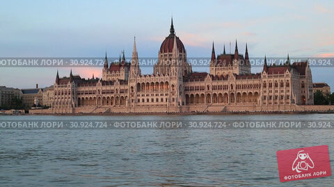 Купить «Beautiful evening view of the Hungarian Parliament Building and the Danube River at sunset in Budapest», видеоролик № 30924724, снято 3 июня 2019 г. (c) Яна Королёва / Фотобанк Лори