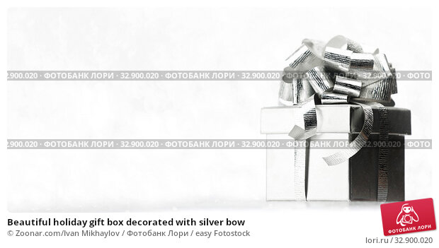 Beautiful holiday gift box decorated with silver bow. Стоковое фото, фотограф Zoonar.com/Ivan Mikhaylov / easy Fotostock / Фотобанк Лори