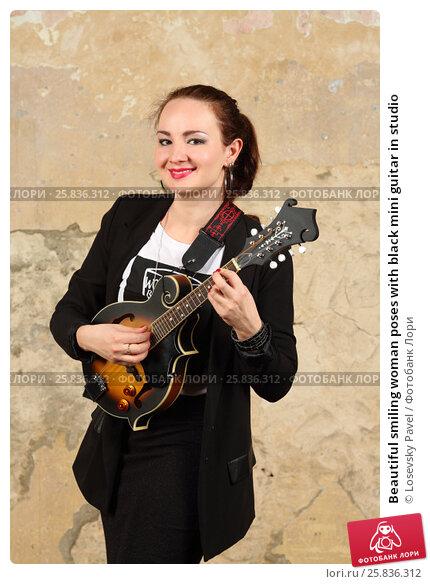 Купить «Beautiful smiling woman poses with black mini guitar in studio», фото № 25836312, снято 9 февраля 2016 г. (c) Losevsky Pavel / Фотобанк Лори