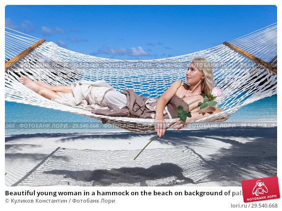 Купить «Beautiful young woman in a hammock on the beach on background of palm trees and the sea», фото № 29540668, снято 18 июня 2011 г. (c) Куликов Константин / Фотобанк Лори