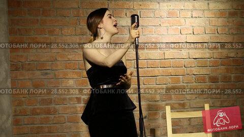 Купить «Beautiful young woman singing on a vintage microphone on brick wall background», видеоролик № 28552308, снято 17 июня 2018 г. (c) Евгений Ткачёв / Фотобанк Лори