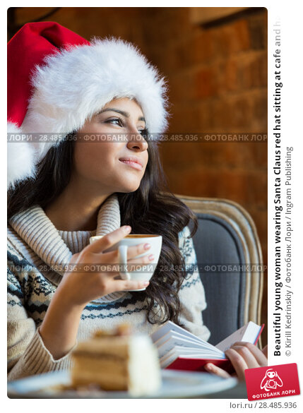Купить «Beautiful young woman wearing Santa Claus red hat sitting at cafe and having hot beverage and tasty cake while reading a book», фото № 28485936, снято 24 сентября 2013 г. (c) Ingram Publishing / Фотобанк Лори